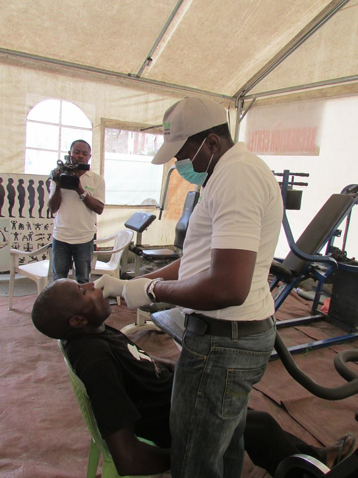 Dr Babajide Onanuga (Oral and Maxillofacial Surgeon) of Motus Health Initiative Administering Anaesthetic Injection Before Extracting Decayed Tooth at Hon. Femi Gbajabiamila Free Medical Programme Powered by Motus Health Initiative in Alaka Housing Estate, off Bode Thomas Street, Surulere, Lagos.