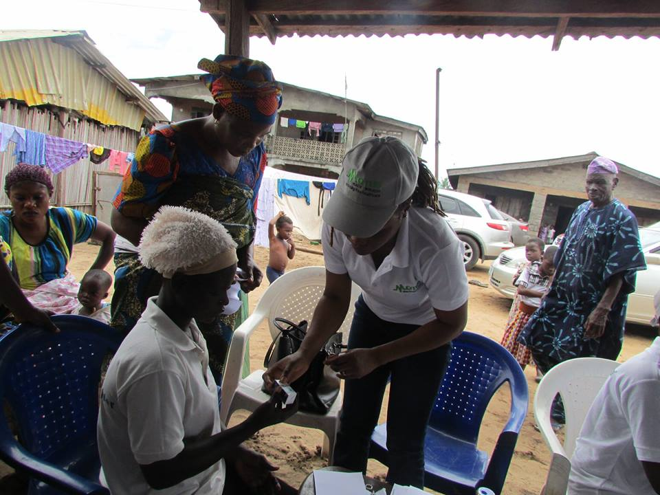 Dr Olubanke Ilo (Consultant Ophthalmologist) of Motus Health Initiative giving out free eye drops at the end of an ophthalmological service in Akodo, Ibeju Lekki, Lagos.