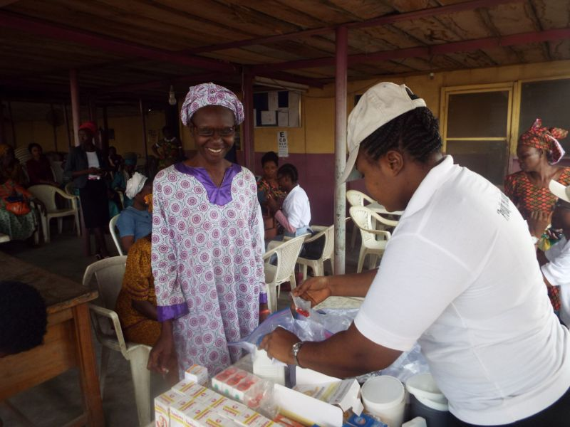 Nurse Abosede Elufowoju of Motus Health Initiative handing over free drugs to a beneficiary at Ire Akari Isolo Free Medical Outreach