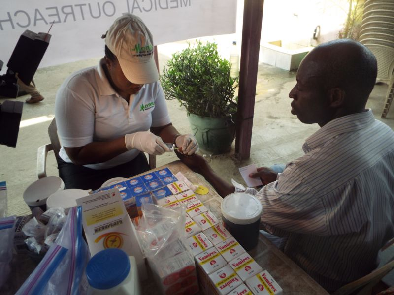 Nurse Abosede Elufowoju of Motus Health Initiative screening the blood glucose level of a patient at Ire Akari Isolo Free Medical Outreach
