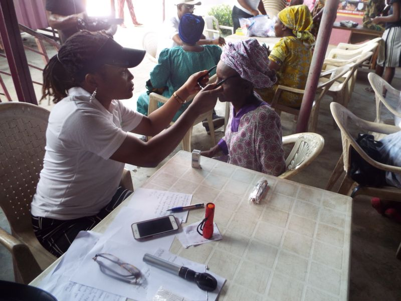 Dr Banke Ilo (Consultant Ophthalmologist) of Motus Health Initiative checking eyeglasses on a patient at Ire Akari Isolo Free Medical Outreach