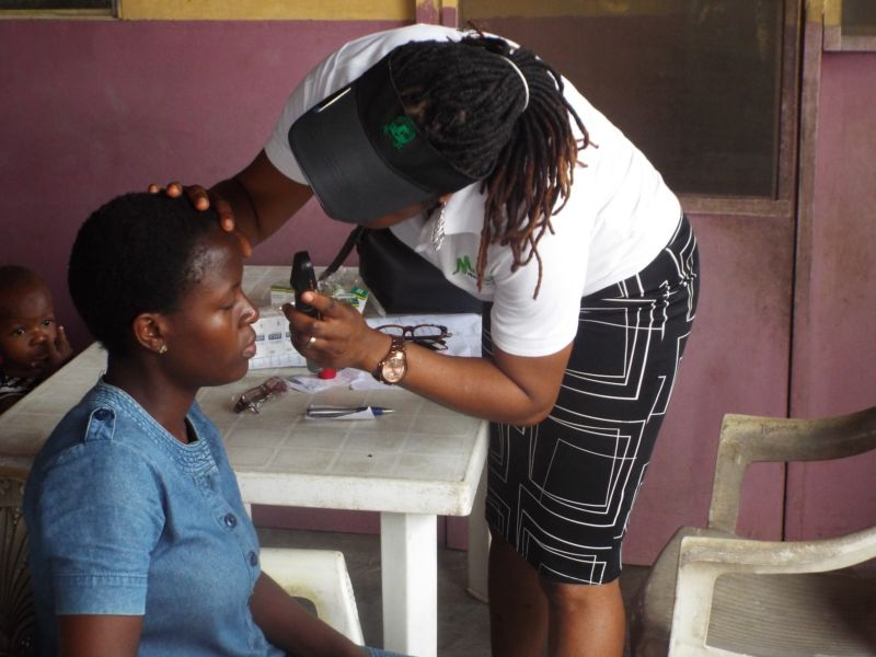 Dr Banke Ilo (Consultant Ophthalmologist) of Motus Health Initiative performing ocular screening at Ire Akari Isolo Free Medical Outreach