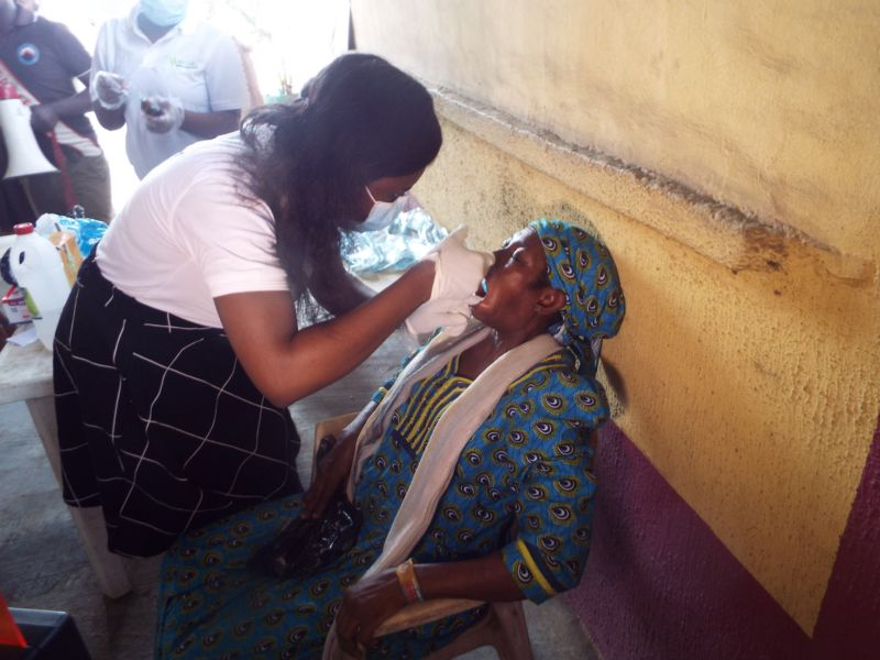Dr Shola Agbogidi (Oral & Maxillofacial Surgeon) of Motus Health Initiative administering anesthetic prior to dental extraction at Ire Akari Isolo Free Medical Outreach