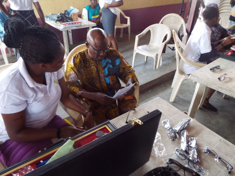 Dr Ogechi Obidike (Optometrist) of Motus Health Initiative conducting reading test after giving free eyeglasses at Ire Akari Isolo Free Medical Outreach