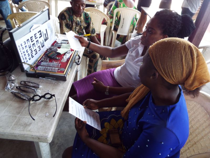 Dr Ogechi Obidike (Optometrist) of Motus Health Initiative performing visual acuity tests on a beneficiary at Ire Akari Isolo Free Medical Outreach.DSCF2520