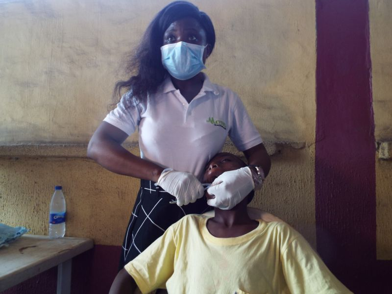 Dr Shola Agbogidi (Oral & Maxillofacial Surgeon) of Motus Health Initiative performing dental extraction at Ire Akari Isolo Free Medical Outreach
